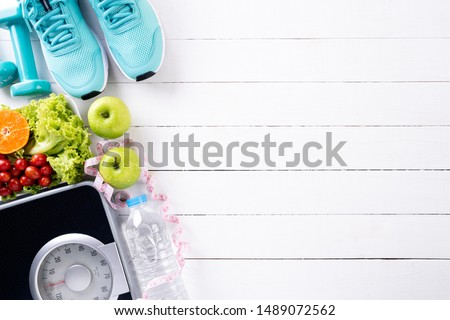 Healthy lifestyle, food and sport concept. Top view of athlete's equipment Weight Scale measuring tape blue dumbbell, sport water bottles, fruit and vegetables on white wooden background. #1489072562
