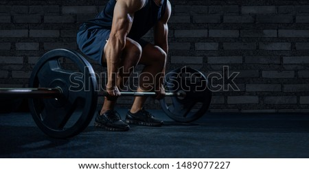 Close up of handsome bodybuilder guy prepare to do exercises with barbell in a gym.bodybuilder's hand is lifting the barbell and exercising in the gym.low key #1489077227
