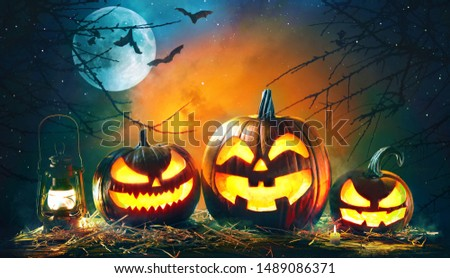 Halloween pumpkin head jack lantern with burning candles in scary deep night forest #1489086371