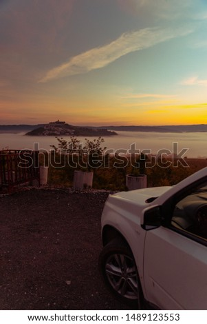 car travel concept view of sunrise over city on the top of the hill summer time
