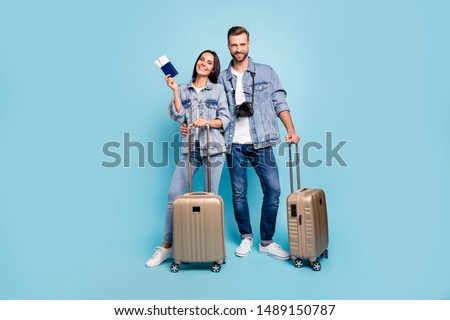 Full length photo of married people holding trolley hug embrace wear stylish denim jeans jackets isolated over blue background #1489150787