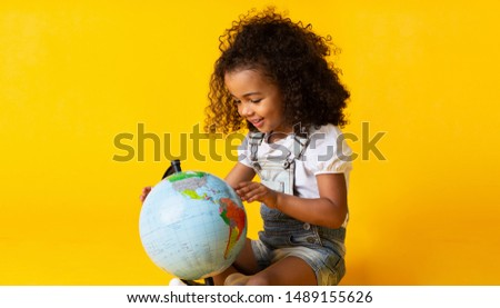 Cute little girl looking at earth globe over yellow studio background Royalty-Free Stock Photo #1489155626