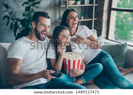 Portrait of nice attractive lovely positive glad cheerful cheery family wearing casual white t-shirts jeans denim sitting on sofa having fun watching funny video enjoying spending free time #1489157471