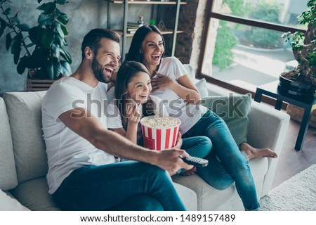 Portrait of nice attractive lovely positive glad cheerful cheery family wearing casual white t-shirts jeans denim sitting on divan having fun watching video switching channel spending free time #1489157489