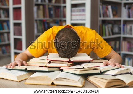 Student studying hard exam and sleeping on books in library, free space #1489158410