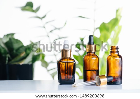 Transparent cosmetic amber glass dropper bottles over green plants on white background. Vials with pipette plastic caps for essential oils, perfumes and skincare substances. Three in a row. #1489200698