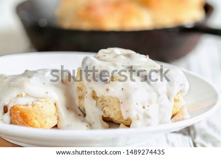 American biscuits from scratch covered with thick white sausage gravy. Selective focus with cast iron skillet / pan in the background over a white table.  Royalty-Free Stock Photo #1489274435