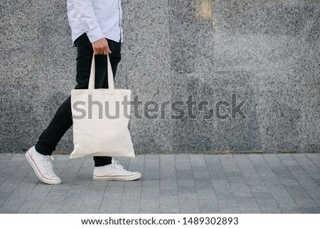 Young man holding white textile eco bag against urban city background. . Ecology or environment protection concept. White eco bag for mock up. Royalty-Free Stock Photo #1489302893