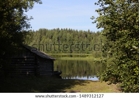 Log cabin on the shore of the pond and a wooden fishing boat.Mirror image of the forest in the lake.Bathhouse near water.Summer holidays in the wildlife of Karelia.Quiet relaxation and privacy.