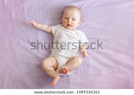 Portrait of cute adorable smiling white Caucasian baby girl boy with blue eyes four months old lying on bed looking at camera. View from top above. Happy childhood lifestyle. #1489336361