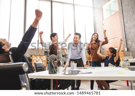 Business people smile and raise hands up, feeling happy, complete finish job, teamwork successful/achievement working in office concept #1489465781