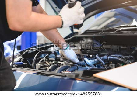 Asian male mechanic hold and shining flashlight to examine car engine problem in front of automotive vehicle car hood. Safety inspection check service maintenance for customer before long road trip #1489557881