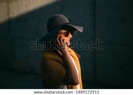 Pretty woman with hat using phone in autumn #1489572911