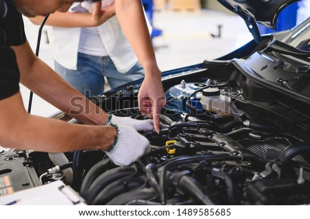 Asian male auto mechanic examine car engine breakdown problem in front of automotive vehicle car hood with female customer. Safety technical inspection care check service maintenance for road trip #1489585685