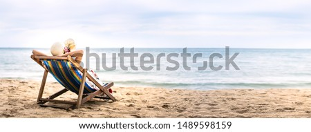 Summer beach holiday, Young asia woman relaxing on beach chair arm up her hand with floppy hat. Background banner with copy space. Pattaya, Thailand #1489598159