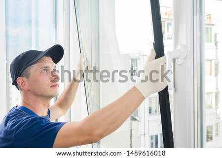 master puts a new double-glazed window in a plastic window #1489616018