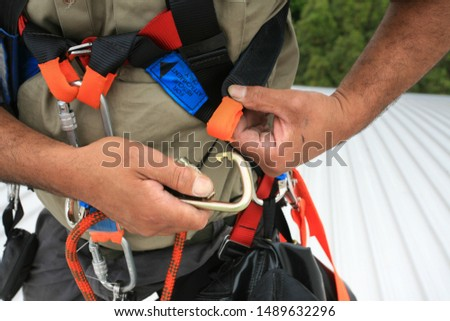 Close up pic of male industrial rope access worker wearing fall arrest, fall restraint safety protection harness clipping Carabiner into side safety harness loop prior work, construction building site