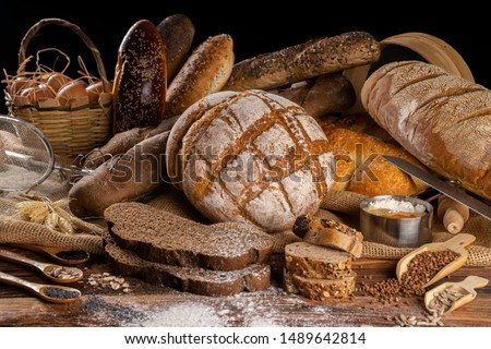 Assortment of baked bread on wooden table background Royalty-Free Stock Photo #1489642814