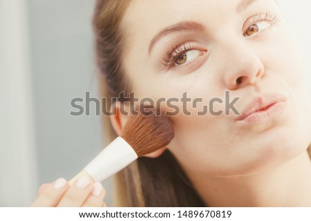 Woman face painting. Girl applying rouge or bronzing powder with brush to her skin in bathroom. Makeup cosmetics and beauty procedures. #1489670819