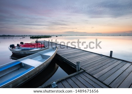 boat at pier on big lake during sunrise in summer #1489671656