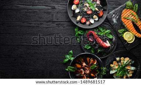 Set of Seafood Dishes. Seafood on a plate. On a black wooden background. Top view. Free copy space. #1489681517