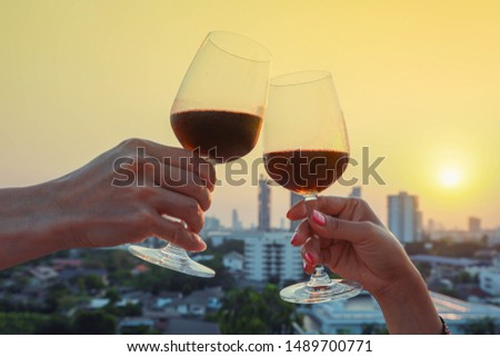 Close up on hands holding red wine glass on balcony during sunset, celebration concept #1489700771