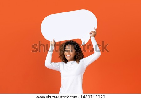Happy young African American woman in plain white long sleeve t-shirt holding empty speech bubble isolated on orange  background Royalty-Free Stock Photo #1489713020