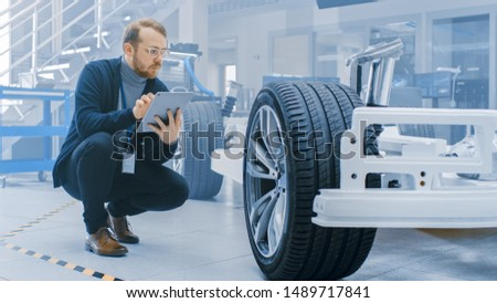 Engineer with Glasses and Beard Works on a Tablet Computer Next to an Electric Car Chassis Prototype with Wheels, Batteries and Engine in a High Tech Development Laboratory. #1489717841