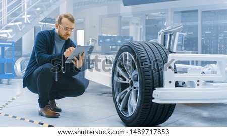 Engineer with Glasses and Beard Works on a Tablet Computer Next to an Electric Car Chassis Prototype with Wheels, Batteries and Engine in a High Tech Development Laboratory. #1489717853