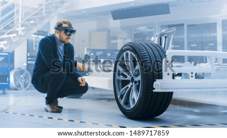 Automotive Engineer Working on Electric Car Chassis Platform, Using Augmented Reality Headset. In Innovation Laboratory Facility Concept Vehicle Frame Includes Wheels, Suspension, Engine and Battery. #1489717859