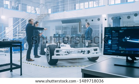 Automotive Design Engineers Talking while Working on Electric Car Chassis Prototype. In Innovation Laboratory Facility Concept Vehicle Frame Includes Wheels, Suspension, Engine and Battery. #1489718036