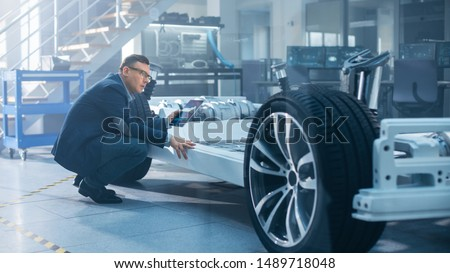 Engineer with Glasses Works on a Tablet Computer Next to an Electric Car Chassis Prototype with Wheels, Batteries and Engine in a High Tech Development Laboratory. #1489718048
