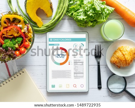 Calories counting, diet , food control and weight loss concept. tablet with Calorie counter application on screen at dining table with salad, fruit juice, bread and vegetable #1489722935