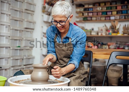 Good looking senior female potter working on pottery wheel while sitting  in her workshop Royalty-Free Stock Photo #1489760348