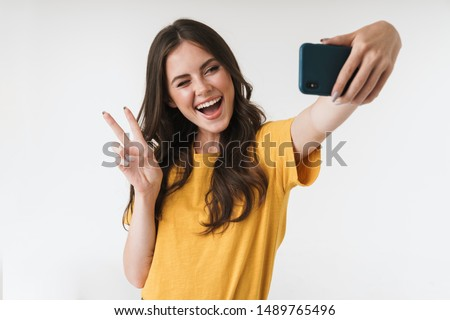 Image of beautiful brunette woman laughing and showing peace sign while taking selfie photo on cellphone isolated over white background