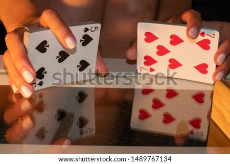 Woman shuffling a deck of cards with a reflection of the hands and cards shown on a glass table #1489767134