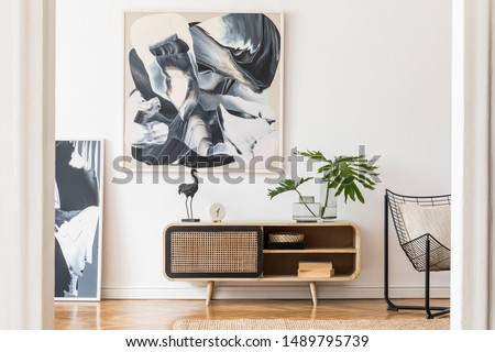 Modern design home interior of living room with wooden commode, design black armchair, tropical leafs and elegant accessories. Stylish home decor. Mock up abstract paintings on the wall. Template.