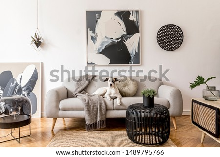 Stylish and scandinavian living room interior of modern apartment with gray sofa, design wooden commode, black table, lamp, abstract paintings on the wall. Beautiful dog lying on the couch. Home decor. Royalty-Free Stock Photo #1489795766