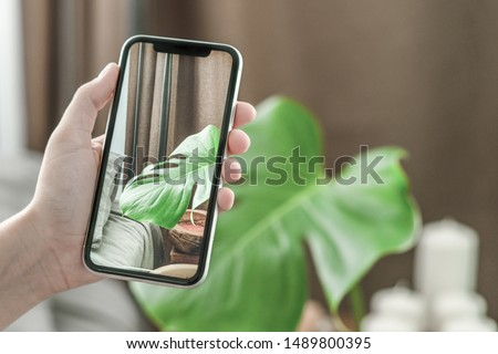 Woman hands using mobile phone takes photo at hotel room cozy bedroom blurred background