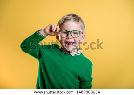 Portrait of blond little boy in green sweater and glasses. Kid at eye sight test. Stylish child holding glasses and looking at camera. Vision, eyesight measurement for school children. Back to school. #1489808654