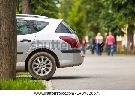 Kyiv, Ukraine - August 25, 2018: Car parked on green lawn in pedestrian zone with walking people on summer day. #1489828679