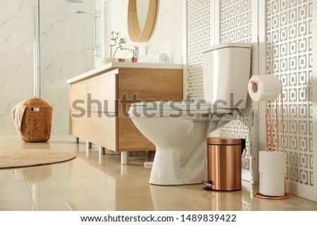 Toilet bowl near wooden screen in modern bathroom interior #1489839422