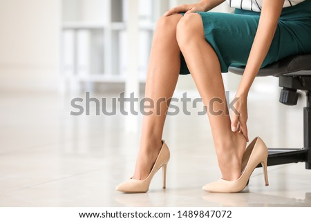 Young woman feeling ache because of wearing high heels in office Royalty-Free Stock Photo #1489847072