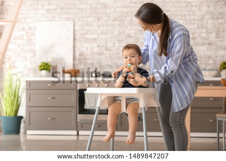 Mother and her little son with nibbler in kitchen at home #1489847207
