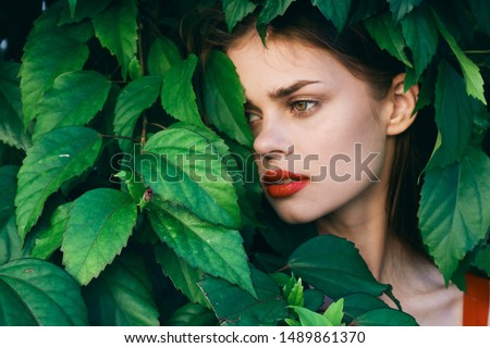 beautiful woman hid in green bushes bright makeup cropped view                     #1489861370