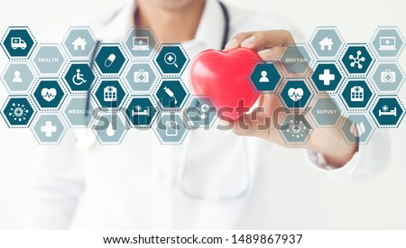 Medicine doctor and stethoscope holding red heart shape in hand touching icon medical network connection with modern virtual screen interface, Healthcare medical technology network concept