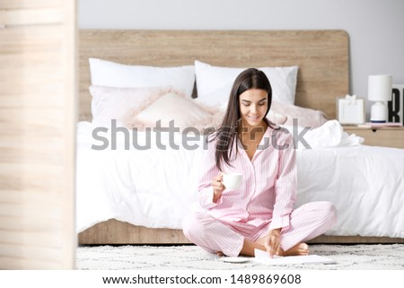 Morning of beautiful young woman drinking coffee while reading book in bedroom #1489869608