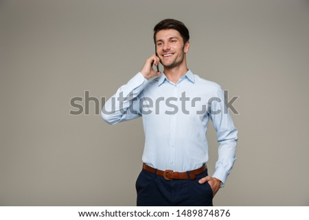 Image of happy masculine man wearing formal clothes smiling and talking on cellphone isolated over gray background #1489874876