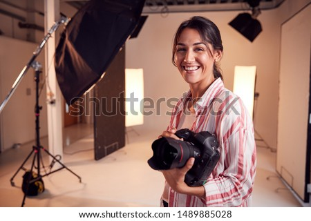 Portrait Of Smiling Female Photographer Standing In Studio With Camera And Lighting Equipment #1489885028