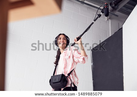 Female Sound Recordist Holding Microphone On Video Film Production In White Studio